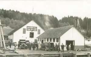 "Three trucks and several people on the wharf at the Alert Bay Cannery. A sign on the building reads ""British Columbia Packers Alert Bay Plant."""
