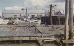 "Docks and fishing boats at the Atlas Camp. The words ""Atlas Camp"" are painted on the side of a building in the background."
