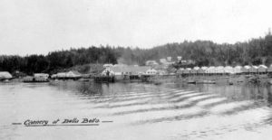 "Cannery buildings in the distance across the water. ""Cannery at Bella Bella"" written at the bottom of the image."