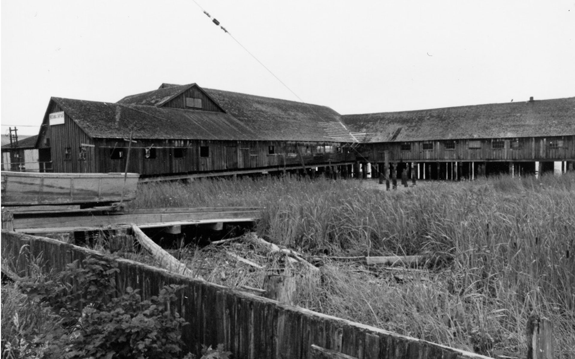 Britannia Shipyards buildings at low tide with grasses in the foreground.