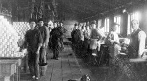 Workers standing at work stations inside a cannery.