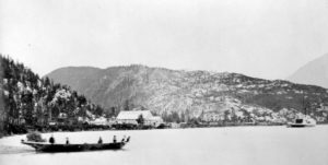 Five figures in a canoe in front of the Croasdaile Cannery.