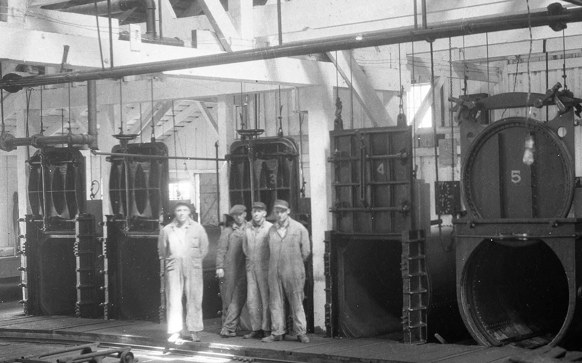 Four men stand in front of five open, empty retorts.