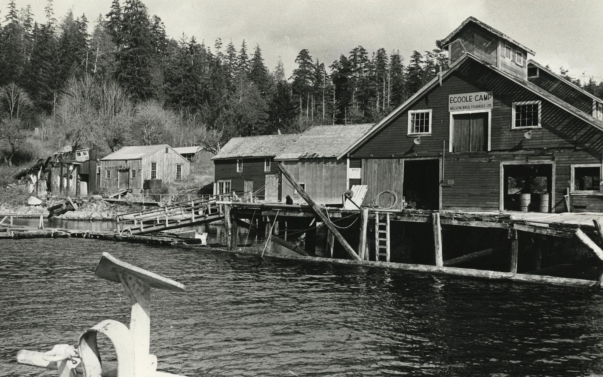 Wooden buildings on pilings with water in the foreground.