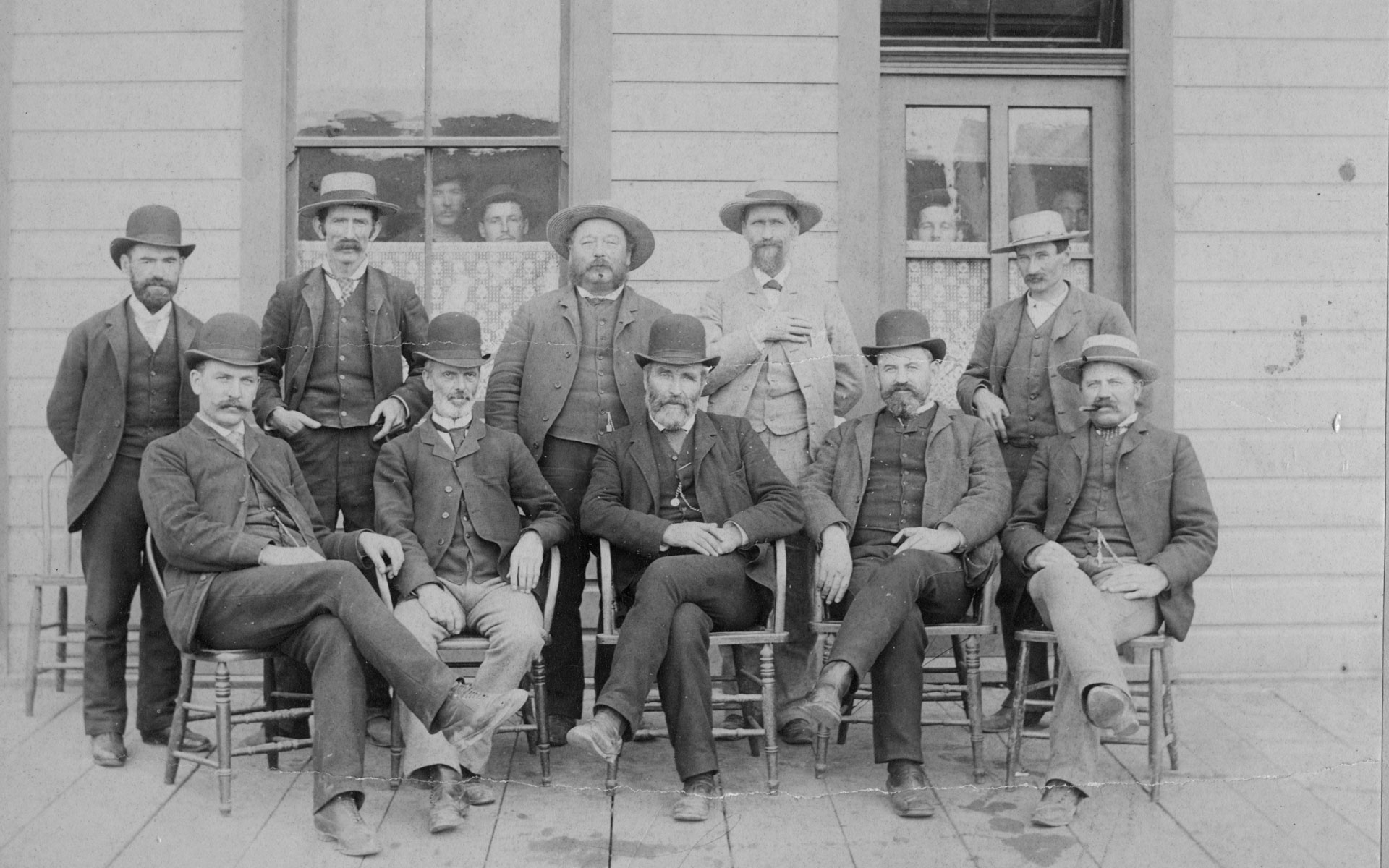 Group portrait with 5 men seated and 5 men standing behind. Four additional people are peaking out the windows of the building behind the men.