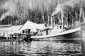 Steamship docked at cannery buildings with land in the background covered in trees.