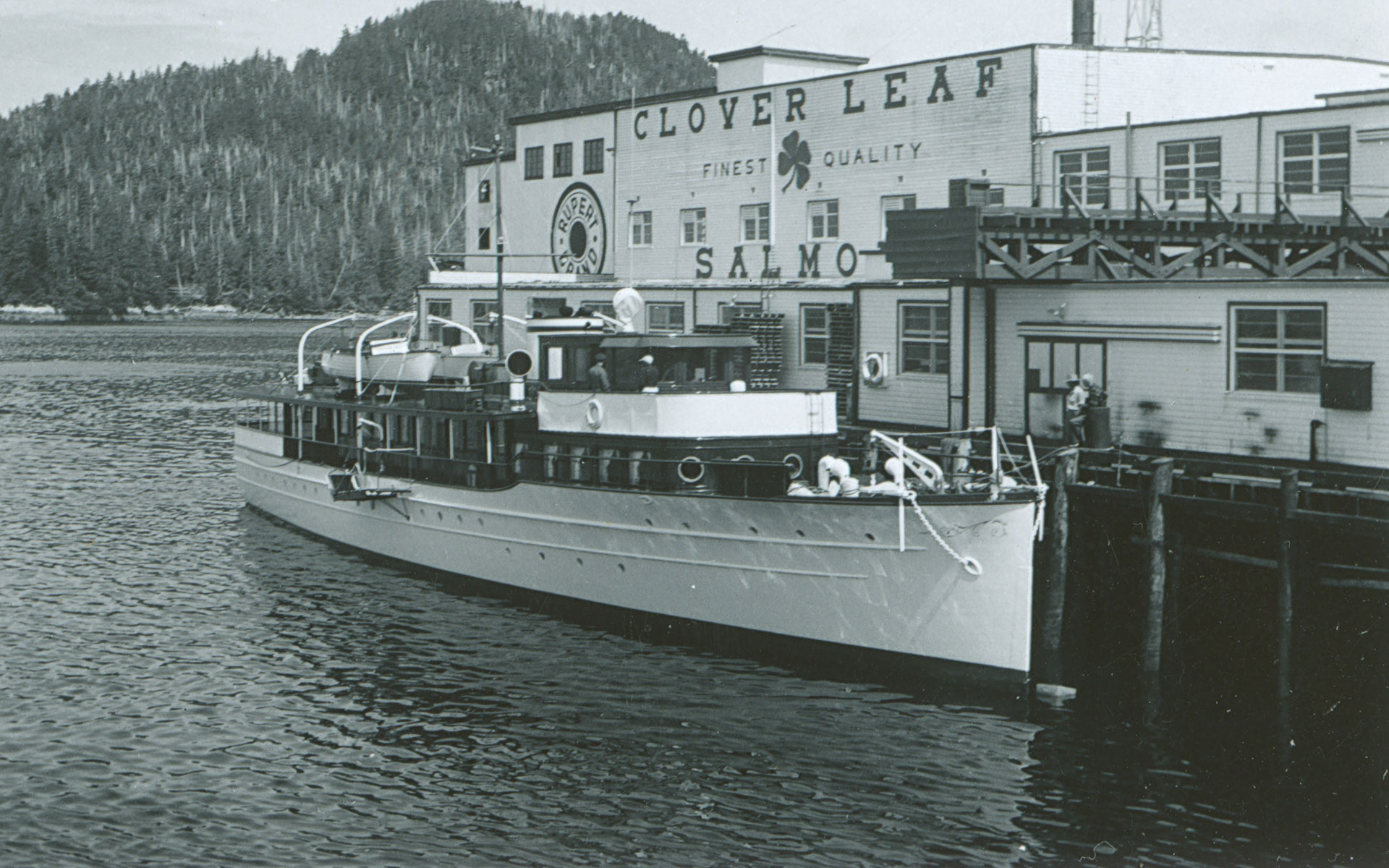"Passenger vessel docked at the Namu cannery. The words ""Clover Leaf finest quality salmon"" and ""Rupert Brand"" are painted on the side of the cannery building."