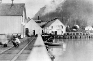 A man is squatting on the wharf with cannery buildings in the background.