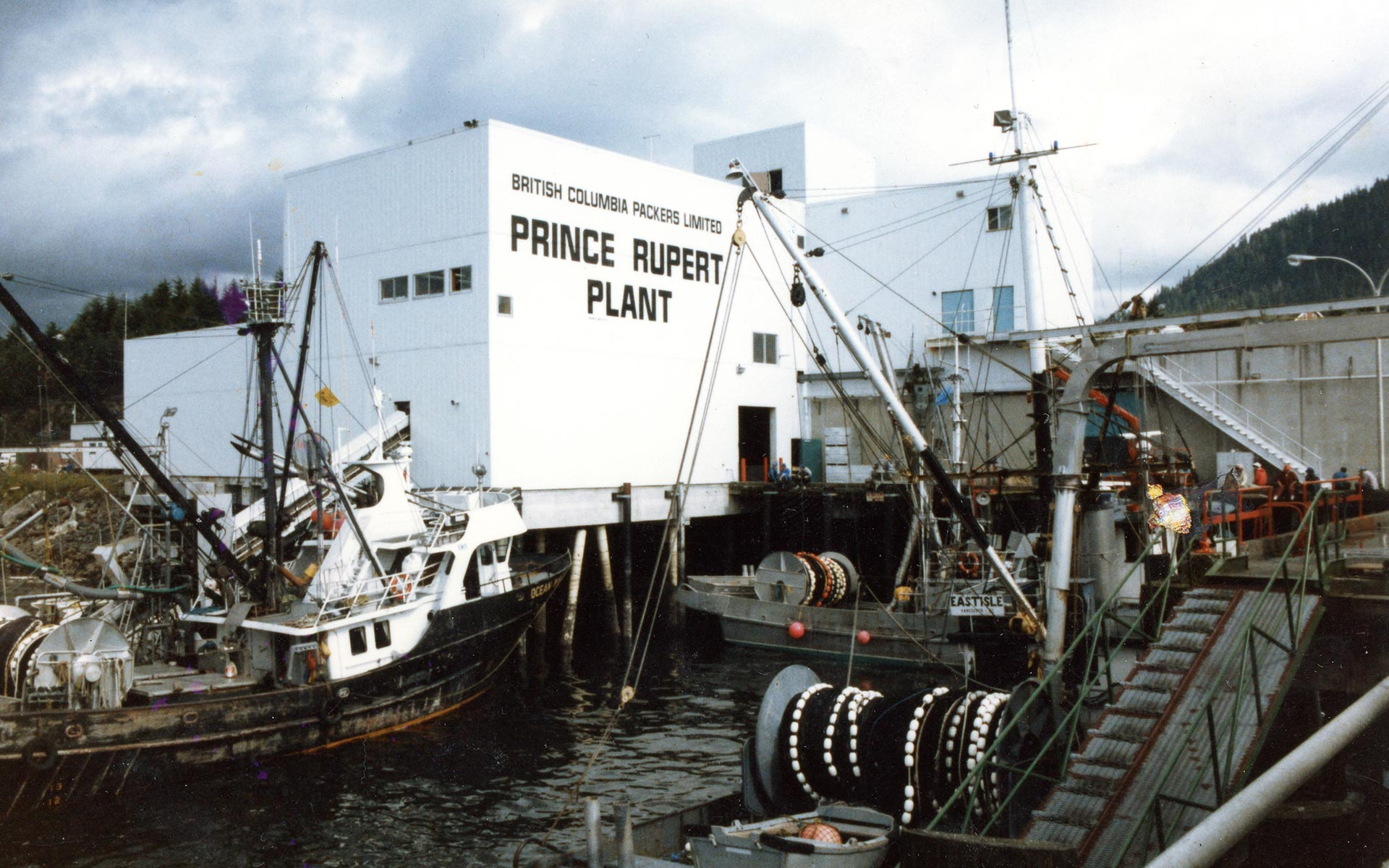 "The Oceanside Cannery with docks and fishing boats in the foreground. The building is painted with the words ""British Columbia Packers Limited Prince Rupert Plant."""