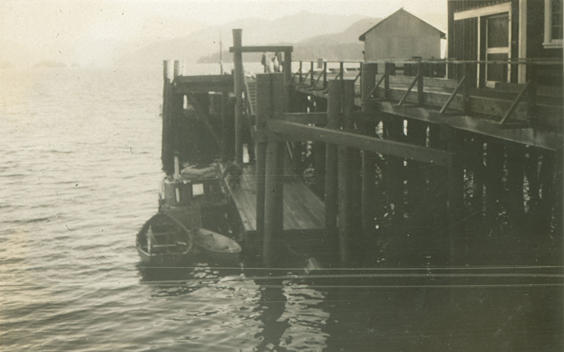 A section of the docks at Nootka with moored fishing boats. Two skiffs and a gillnetter are tied to the dock.