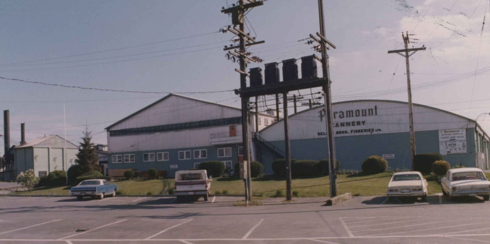 "Paramount cannery buildings as seen across the company parking lot. The words ""Paramount Cannery, Nelson Bros. Fisheries Ltd."" are painted on the side of the building."