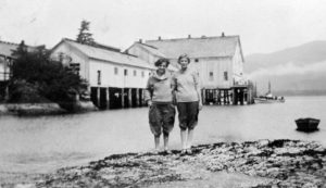 Two women stand together on a rocky point with the cannery buildings directly behind them across the water.