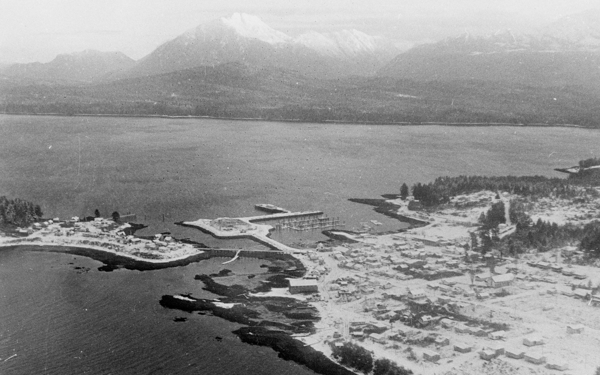 Cannery buildings cover the land in the foreground. Mountains are visible across the water in the background.