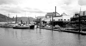 Cannery buildings, docks, and boats with water in the foreground.