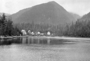 Cannery buildings nestled at the end of a bay with a treed mountain behind.