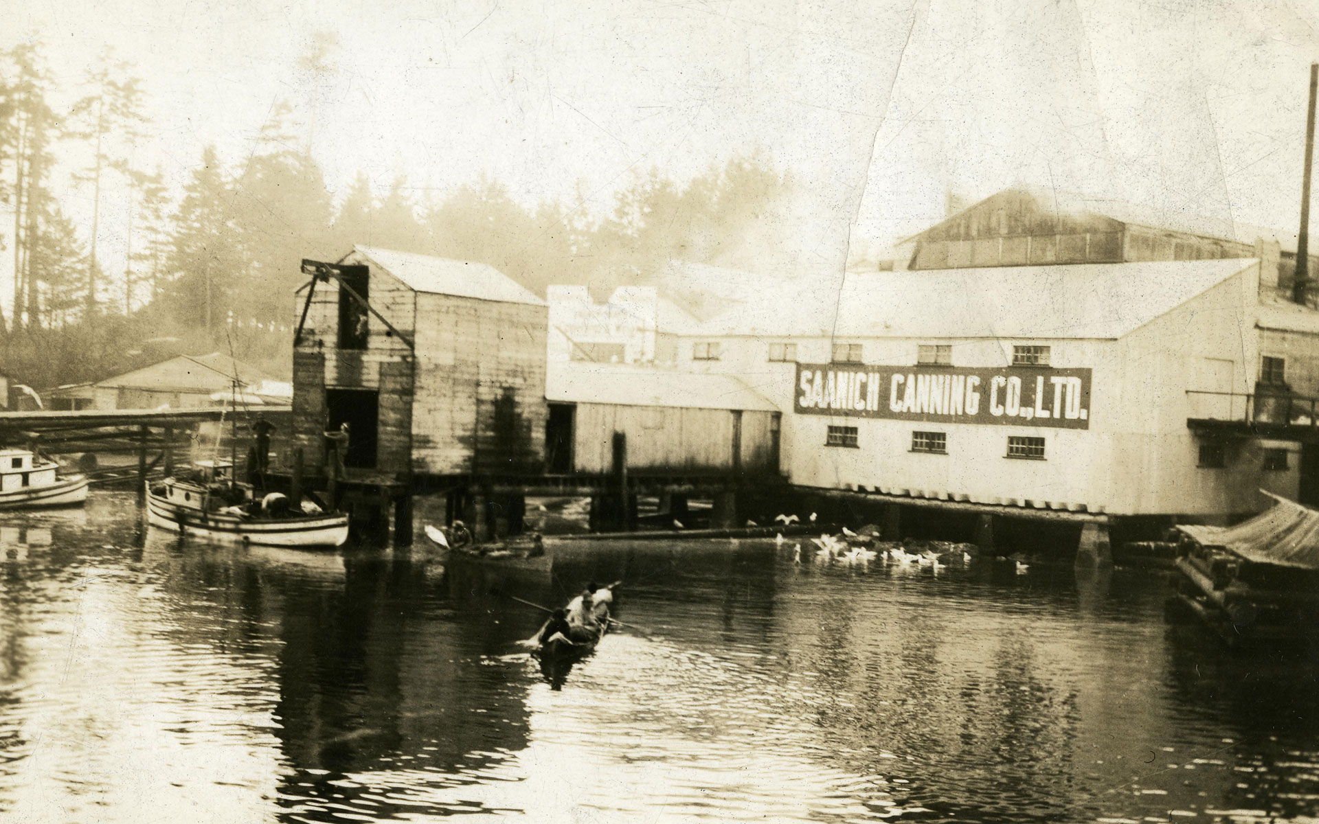 Cannery buildings viewed from the water with skiffs in the foreground.