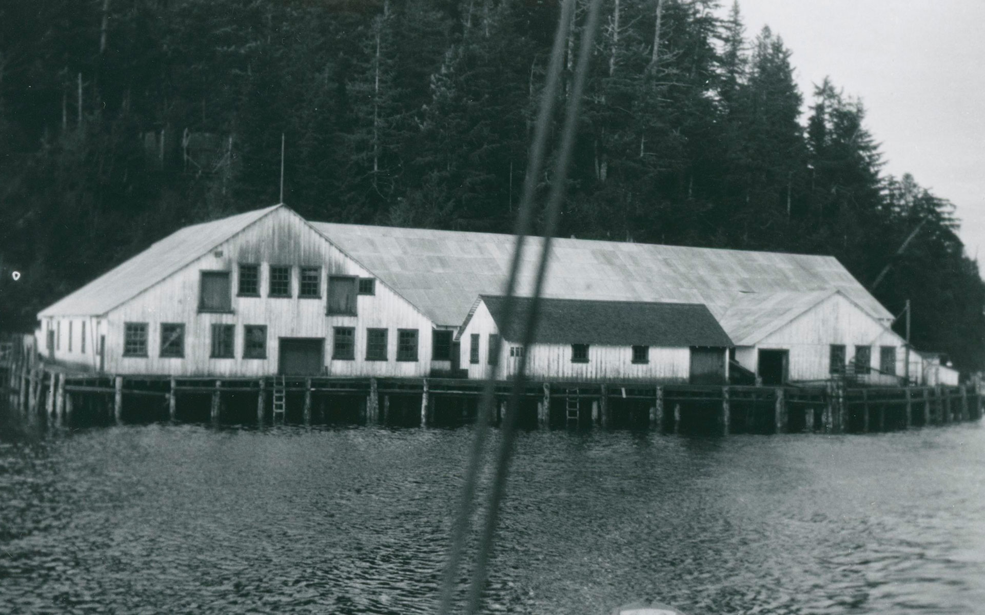 Shushartie Cannery buildings photographed from a boat on the water. Two ropes, part of the rigging of a boat, are visible in the foreground. The cannery sits at the waters edge with a wooden hill behind it.