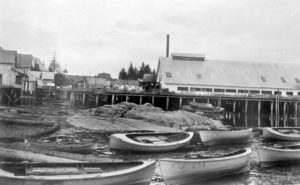 Skiffs are lined up along the beach at low tide in front of cannery buildings.