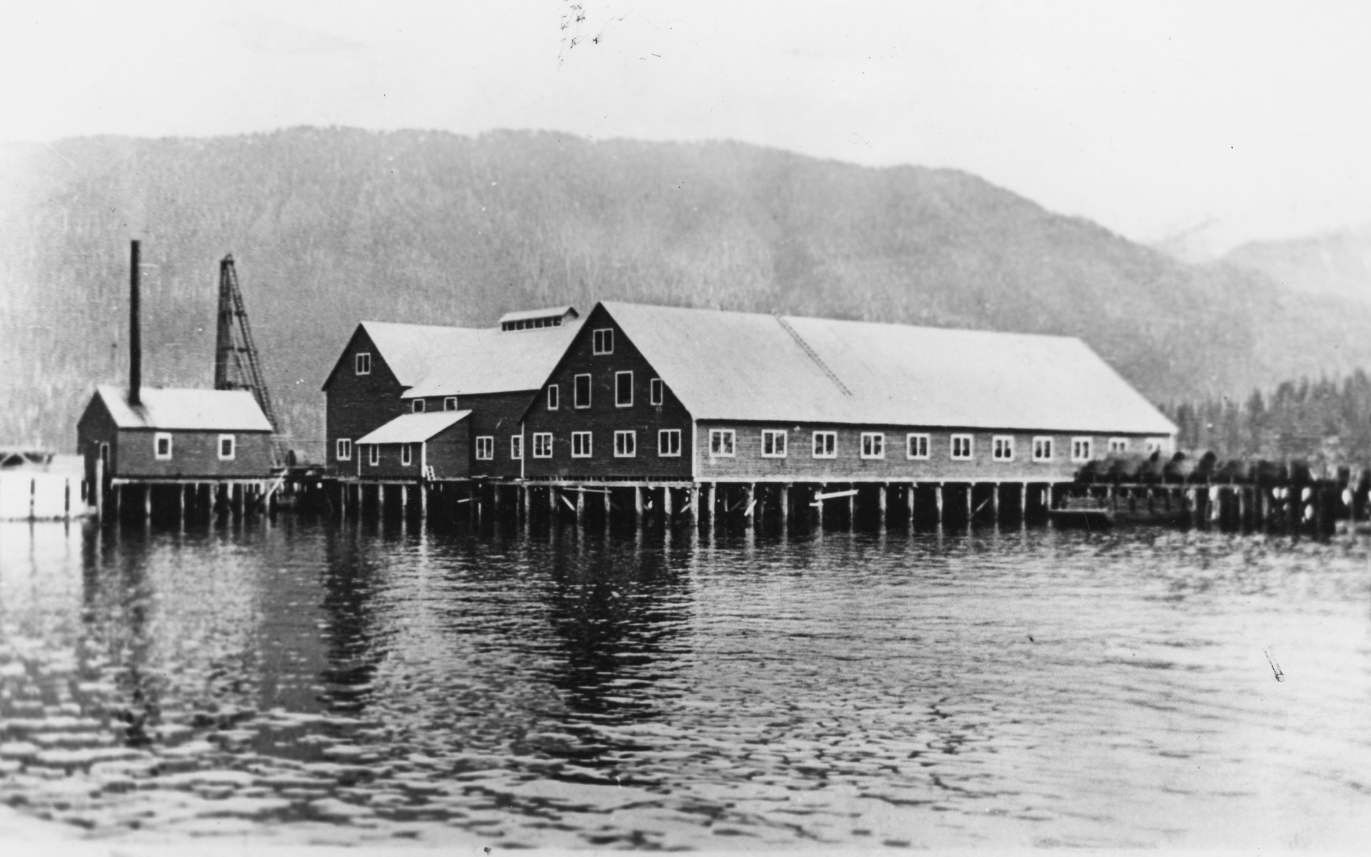 Cannery buildings on pilings over the water.