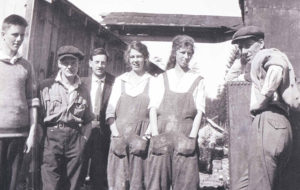 Group of cannery workers standing outside. Two female workers are wearing overalls and have their hands in their pockets.
