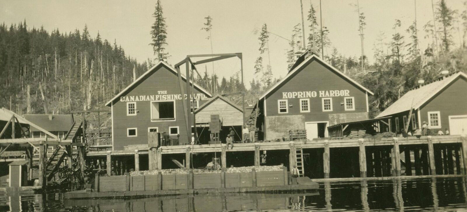 "Men resting on the wharf and working near the fish bins at the Koprino Harbour Cannery. Signs on the buildings read ""The Canadian Fishing Co. Ltd."" and ""Koprino Harbor"""