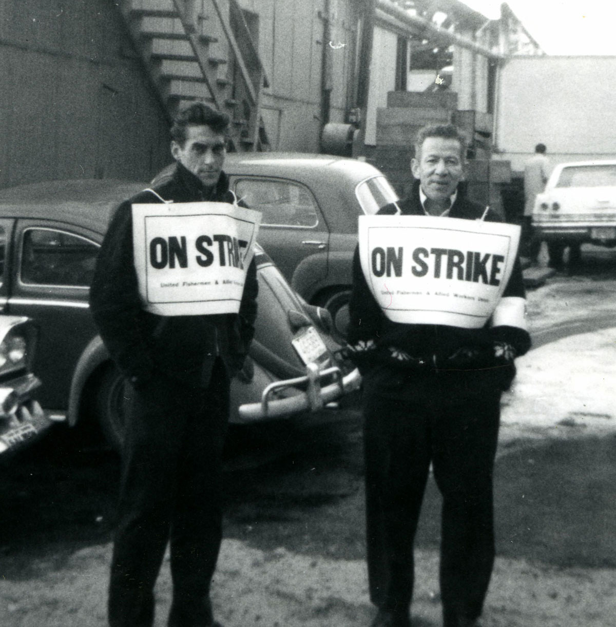 "Two men wearing signs labelled ""on strike"" standing in front of buildings and parked cars"
