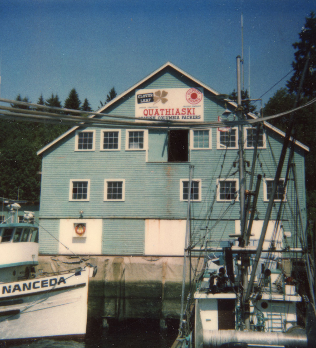 Blue building with two rows of large windows facing the water. Fishing boats in the foreground.