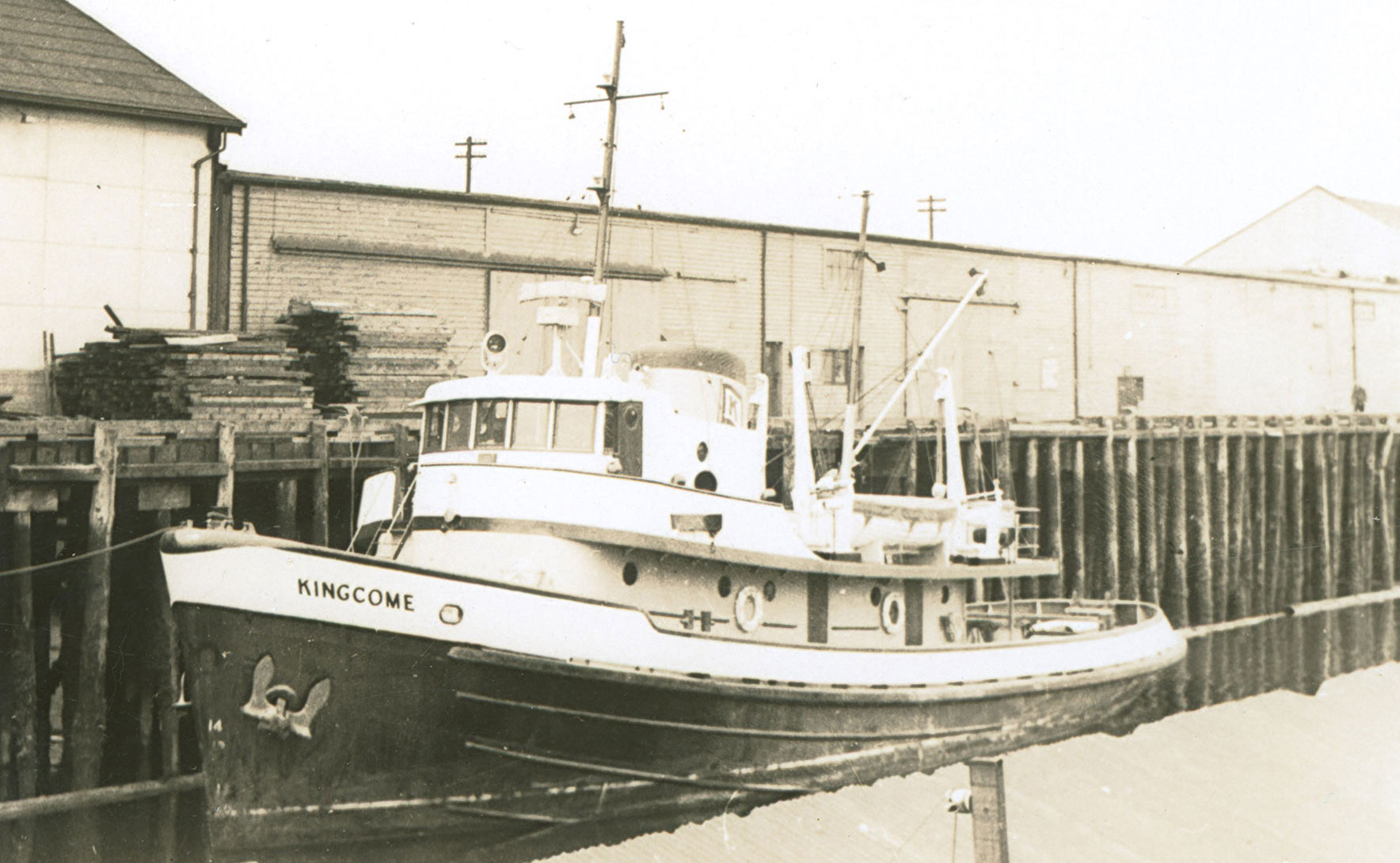 "Vessel named ""Kingcome"" moored at a dock in front of cannery buildings"
