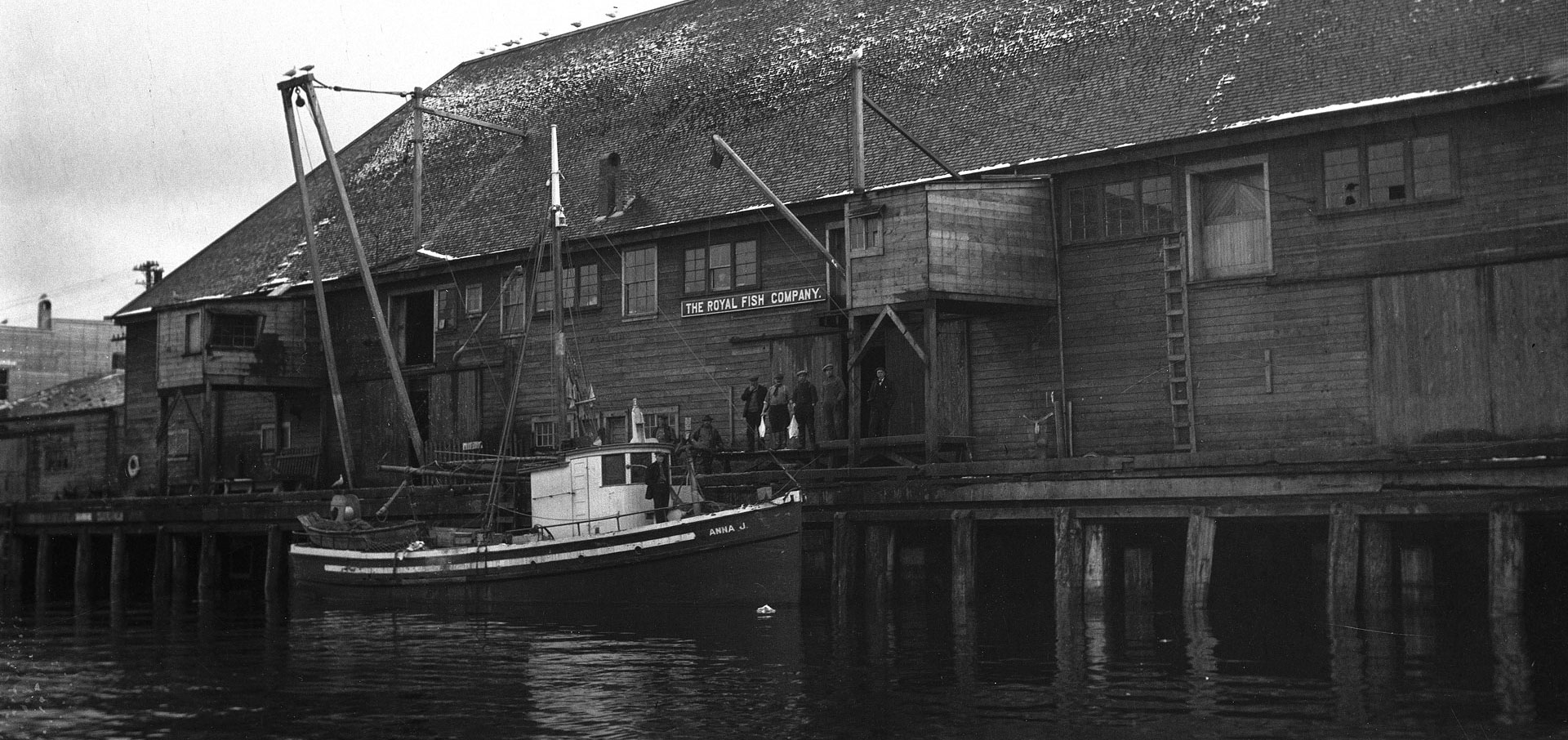 Boat docked at the Royal Fish Company plant. Several men stand by the wooden building holding fish