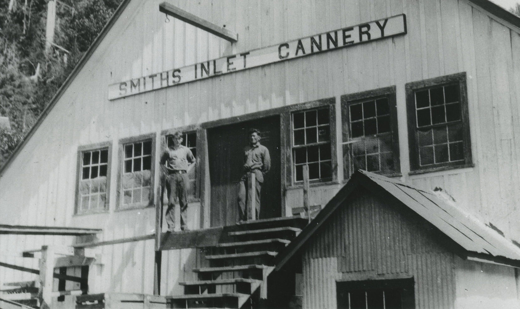 Two men stand at the top of steps leading into the wooden cannery building