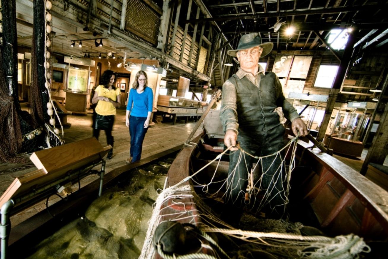 Deux personnes déambulent près d'une exposition à l'intérieur de la conserverie Gulf of Georgia. Il y a un mannequin de pêcheur debout dans un skiff tenant un filet maillant. D'autres expositions sont visibles à l'arrière-plan.