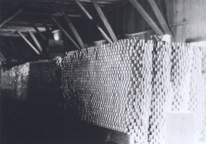 Cans are stacked to the rafters inside a wooden building.